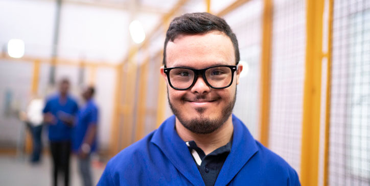 Portrait of smiling special needs employee in industry